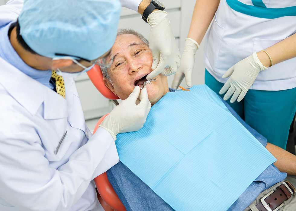 Giám đốc - bác sĩ Tôn Thất Ngọc tựu tay thực hiện thăm khám và lấy mẫu phục hình răng cho khách hàng lớn tuổi